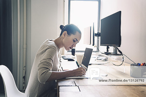 Side view of businesswoman writing while sitting at desk in office