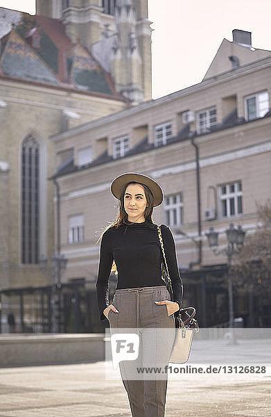 Frau mit Händen in den Taschen  die in der Stadt auf der Straße geht