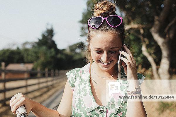 Smiling teenage girl looking down while talking on smart phone