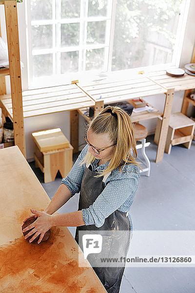 Draufsicht einer Frau  die in einer Töpferwerkstatt arbeitet