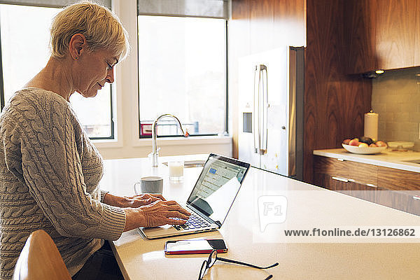 Side view of senior woman typing on laptop while sitting at kitchen table