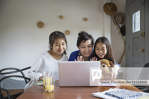 Happy family doing video call with laptop at home