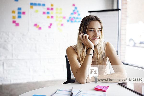 Nachdenklich lächelnde Geschäftsfrau  die im Kreativbüro am Tisch sitzt