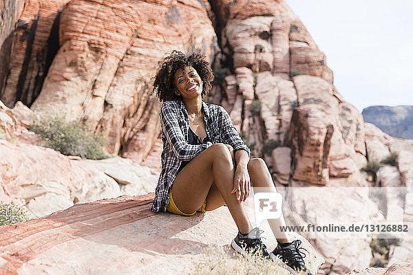 Porträt einer glücklichen Frau  die an einem sonnigen Tag auf einer Felsformation sitzt