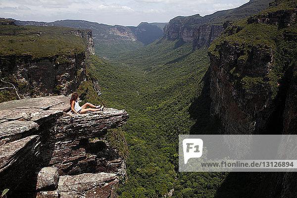 Blick aus mittlerer Entfernung auf eine Frau  die auf einer Klippe im Nationalpark Chapada Diamantina sitzt