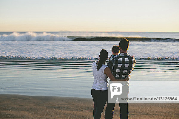 Family looking at view while standing at beach during sunset