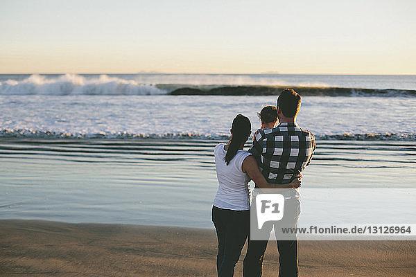 Familie  die bei Sonnenuntergang am Strand steht und auf die Aussicht schaut