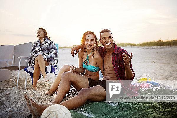 Lächelndes Paar sitzt am Strand gegen den Himmel