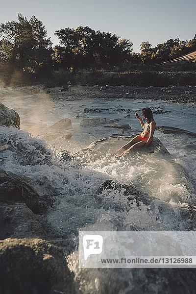 Hochwinkelansicht einer Frau  die auf Felsen sitzt  während sie sich in einem dampfabgebenden Thermalbad erfreut