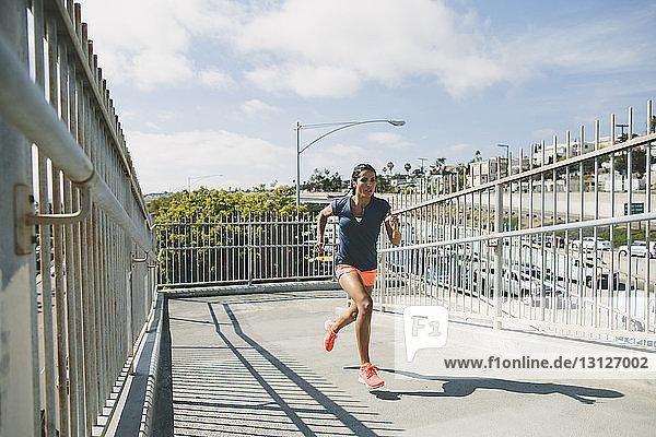 Sportswoman running on footbridge against sky in sunny day
