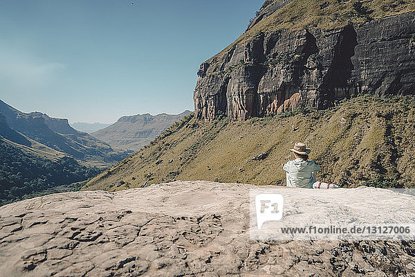 Rückansicht einer Frau  die an einem sonnigen Tag auf einem Berg sitzt