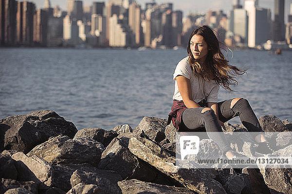 Nachdenkliche Frau sitzt auf Felsen am Strand