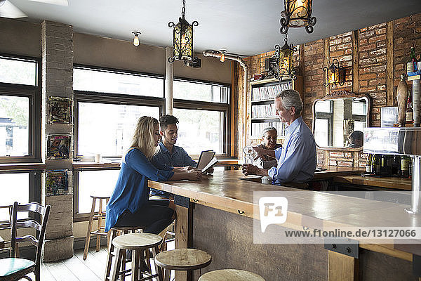 Lächelnder Besitzer im Gespräch mit Kunden  während er an der Theke im Café steht