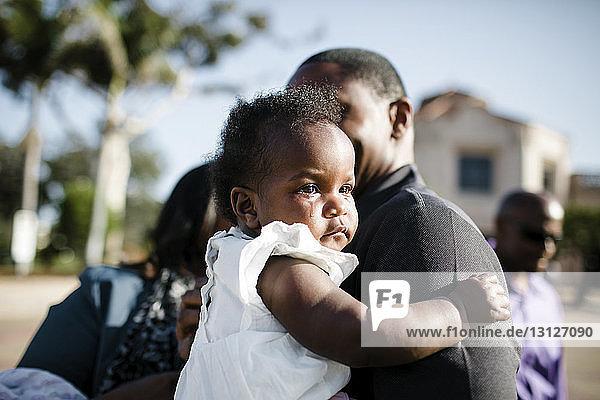 Nahaufnahme eines Vaters  der eine weinende Tochter trägt  während er gegen den Himmel steht