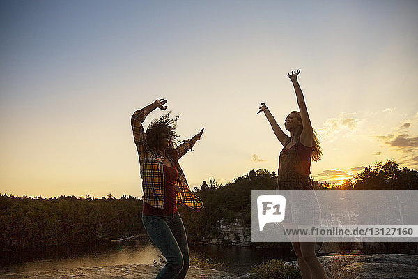 Cheerful female friends enjoying at lakeshore during sunset