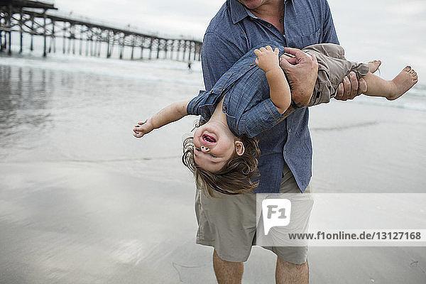 Mitschnitt eines spielerischen Vaters  der seinen Sohn trägt  während er am Strand am Ufer spielt