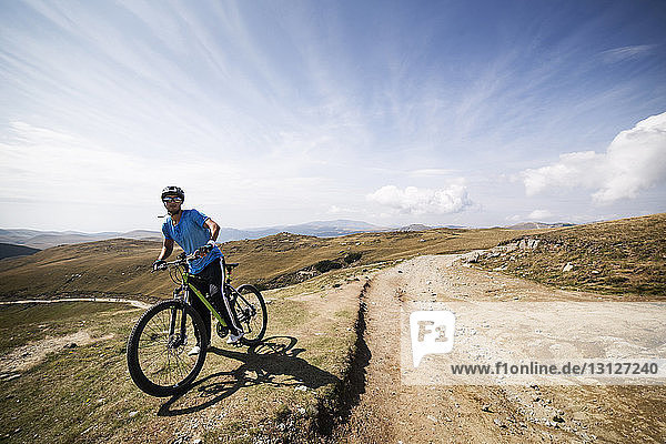 Man with bicycle on mountain against sky