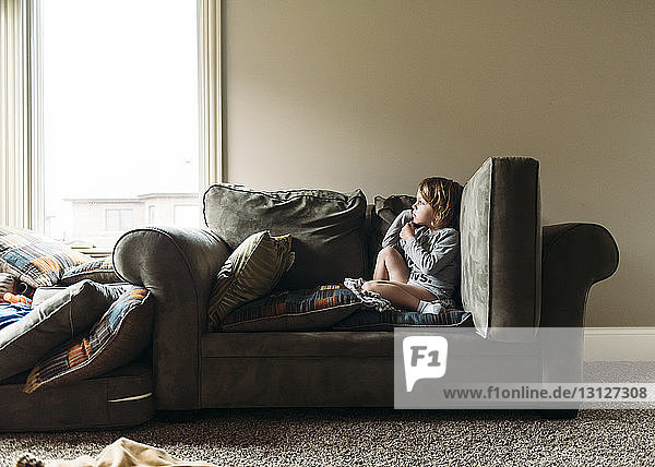 Boy relaxing on sofa at home