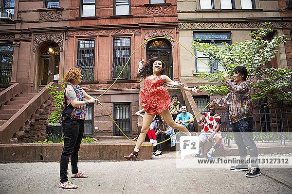 Freunde schauen auf Frau  die auf dem Bürgersteig gegen ein Gebäude Doppel-Holländisch spielt