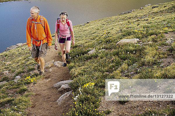 Couple climbing mountain against river