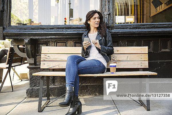 Nachdenkliche Frau hält Smartphone in der Hand  während sie auf einer Bank im Straßencafé sitzt