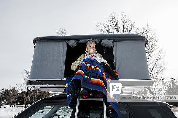 Low angle view of woman knitting while sitting in roof tent on car during winter