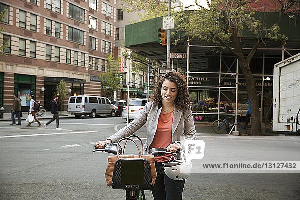 Geschäftsfrau zu Fuß mit Fahrrad auf der Straße