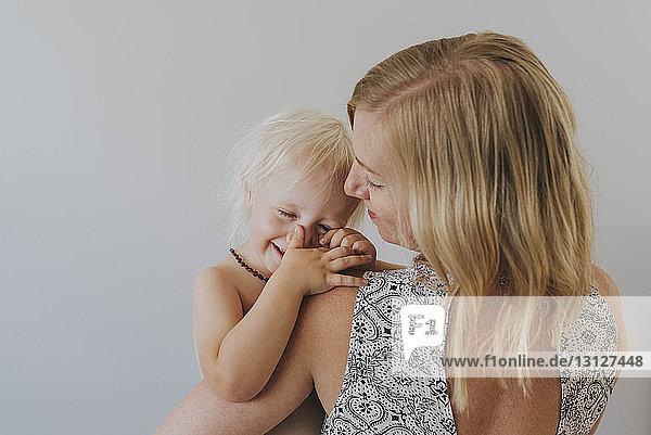 Rückansicht einer Mutter  die eine glückliche Tochter ohne Hemd trägt  vor weissem Hintergrund stehend