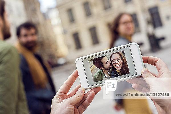 Ausgeschnittene Hände  die ein Smartphone halten  das ein Foto mit Freunden im Hintergrund zeigt