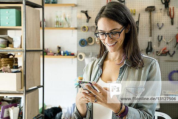 Glückliche Geschäftsfrau benutzt Smartphone im Büro
