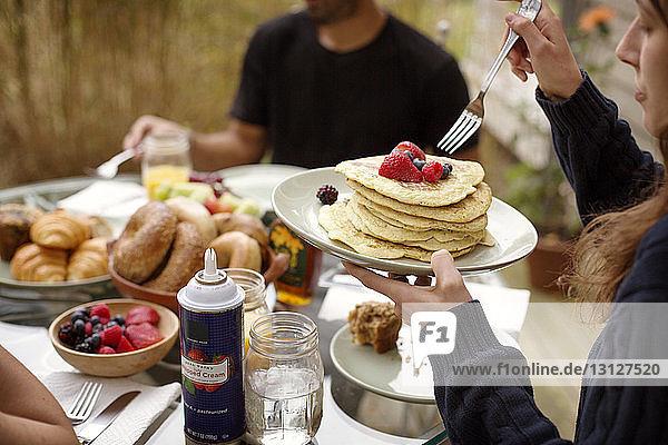 Junge Frau isst Pfannkuchen beim Frühstück mit Freunden