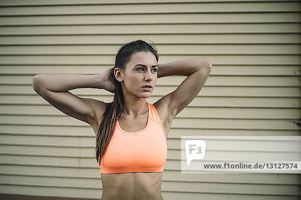 Thoughtful female athlete looking away while standing with hands behind head against corrugated wall