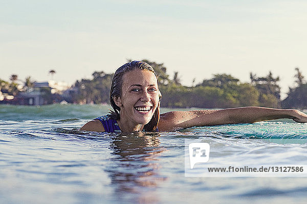 Happy young woman swimming in sea against clear sky