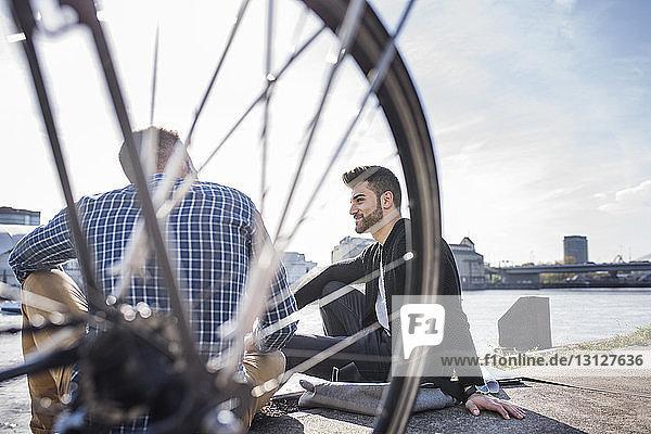 Freunde sitzen mit dem Fahrrad vor dem Kanal vor klarem Himmel