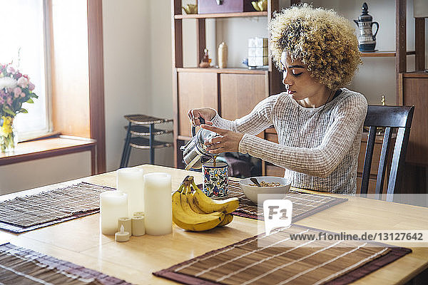 Woman pouring coffee in cup at table in house