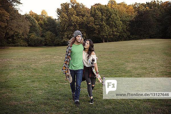 Paar mit Skateboards beim Gehen auf Grasfeld
