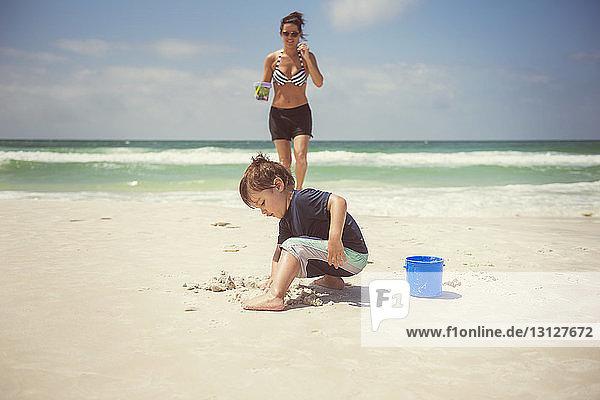 Junge spielt mit Sand  während die Mutter am Strand spazieren geht