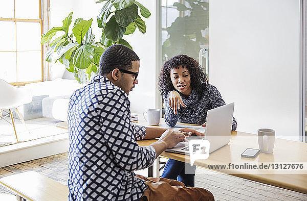 Geschäftsleute schauen auf den Laptop und diskutieren auf dem Tisch im Büro