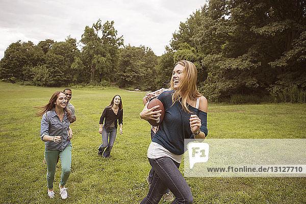 Spielerische Freunde jagen Frau  die auf einem Rasenplatz einen Fussball hält