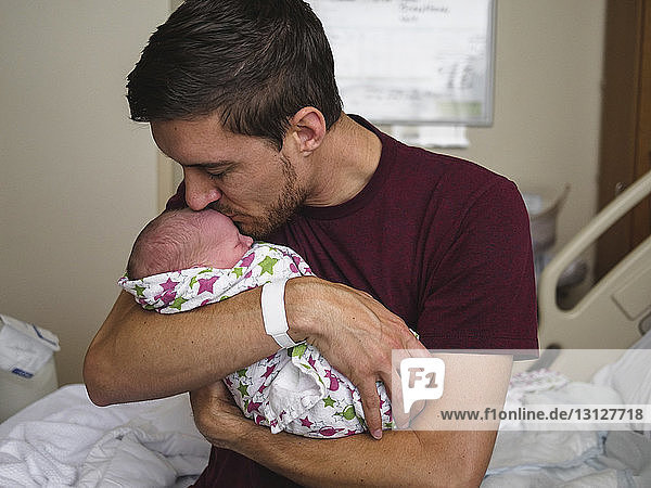 Father kissing newborn son while sitting on bed at hospital