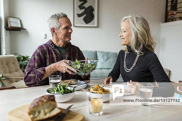 Lächelnder Mann schenkt Frau eine Schüssel Blattgemüse  während er am Esstisch sitzt