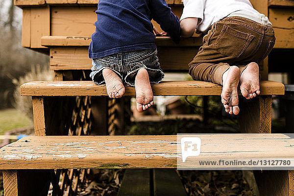 Niedrige Sektion von Brüdern  die auf Stufen auf dem Spielplatz kniend spielen
