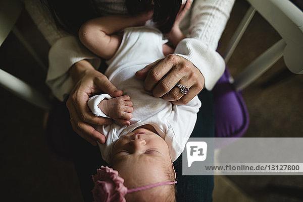 Nahaufnahme einer Mutter  die eine schlafende Tochter zu Hause trägt