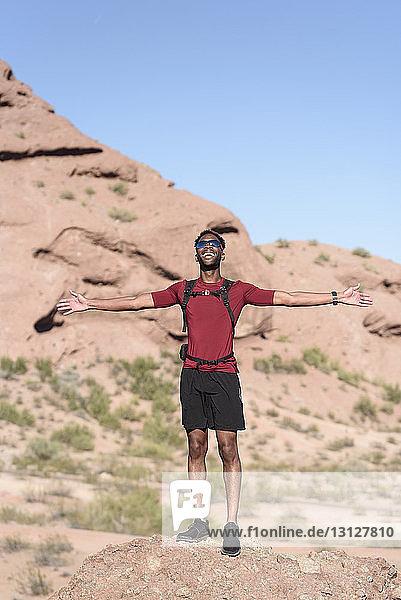 Männlicher Wanderer mit ausgestreckten Armen auf Fels stehend vor strahlend blauem Himmel am sonnigen Tag