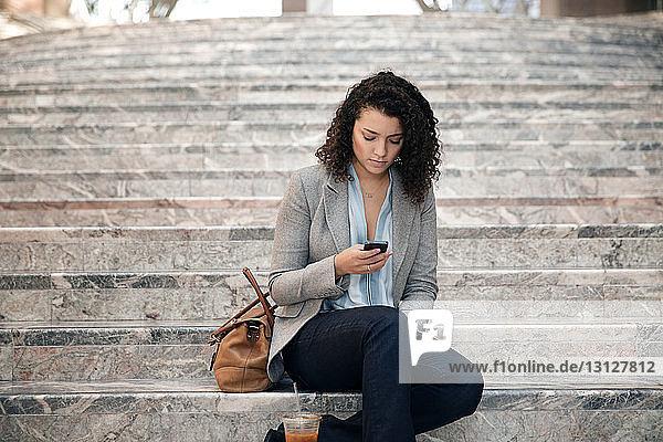 Geschäftsfrau benutzt ein Smartphone  während sie auf einer Treppe im Freien sitzt