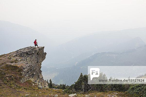 Seitenansicht eines Wanderers  der bei nebligem Wetter auf einer Klippe vor den Bergen steht
