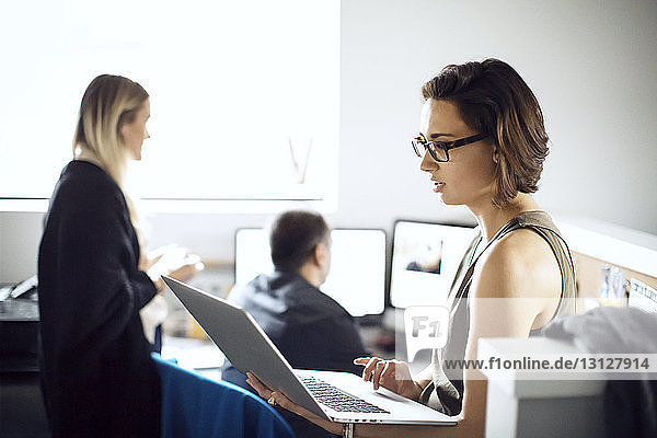 Businesswoman using laptop while colleagues working in creative office