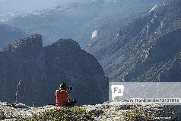 Mann fotografiert  während er auf einer Klippe im Yosemite National Park sitzt