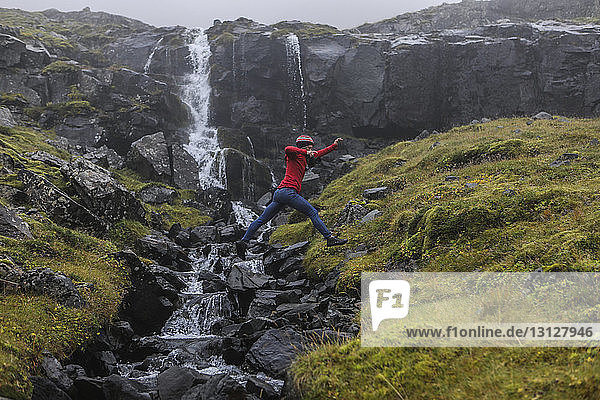 Side view of hiker jumping against waterfall