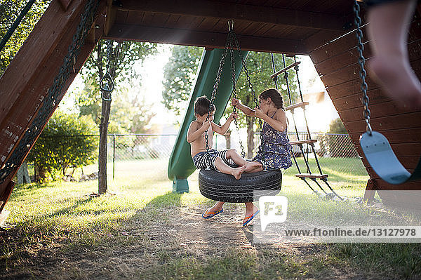Playful siblings swinging on tire swing at playground